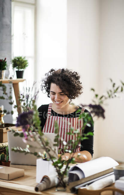 Smiling young woman using laptop in a small shop with plants — Stock Photo