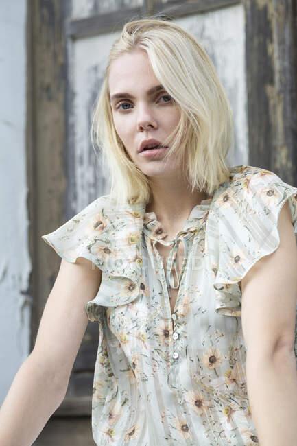 Retrato de una joven rubia con blusa de verano con diseño floral - foto de stock
