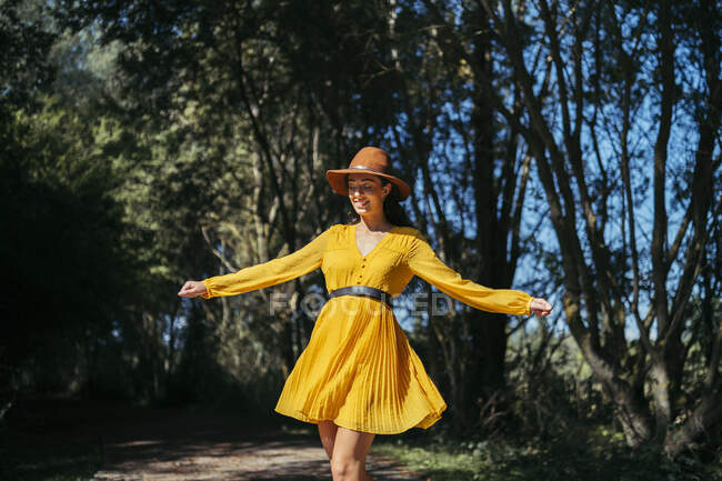 Happy young curly haired woman wearing brown hat and yellow dress walking with open arms and closed eyes — Stock Photo