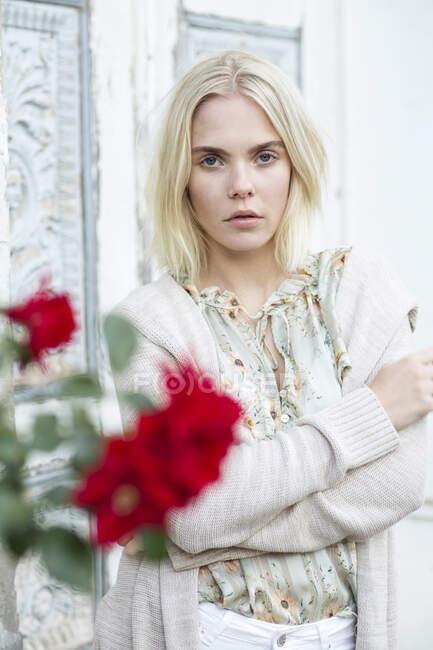 Retrato de una joven rubia con blusa de verano con diseño floral y cárdigan - foto de stock