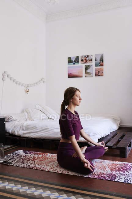 Молодая брюнетка практикует йогу в студенческом общежитии — стоковое фото