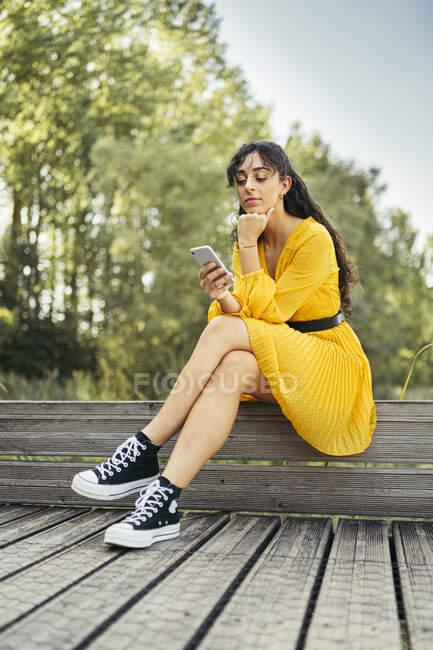 Молода жінка в жовтій сукні і чорних кросівках і за допомогою смартфона на дерев'яному набережній. — стокове фото