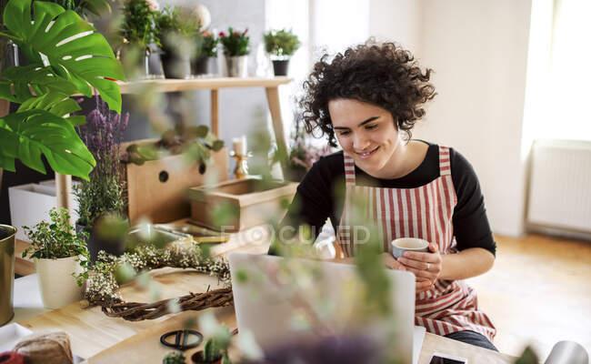 Усміхнена молода жінка користується ноутбуком у маленькому магазині з рослинами. — стокове фото