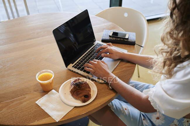 Mujer joven en un café con ordenador portátil mientras desayuna - foto de stock