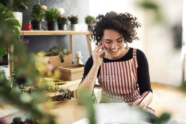 Happy young woman on the phone in a small shop with plants — Stock Photo
