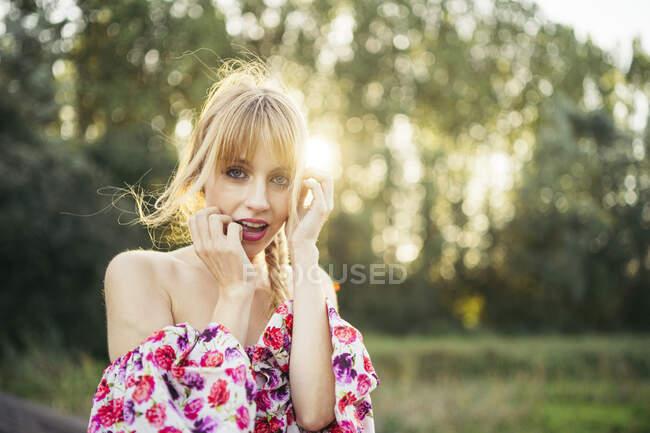Портрет блондинки, одягненої в літню сукню з квітковим дизайном на задньому плані. — стокове фото