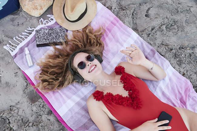 Giovane donna felice sdraiata su un asciugamano sulla spiaggia ad ascoltare musica — Foto stock