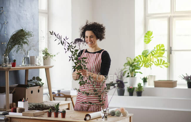 Happy young woman arranging flowers in a small shop — Stock Photo