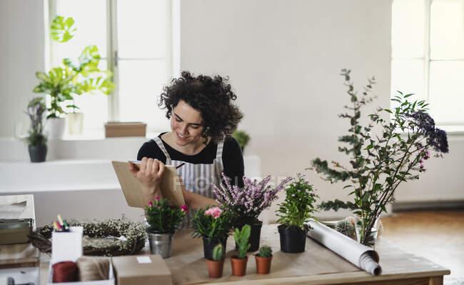 Посмішка молодої жінки з планшетом у маленькому магазині з рослинами. — стокове фото