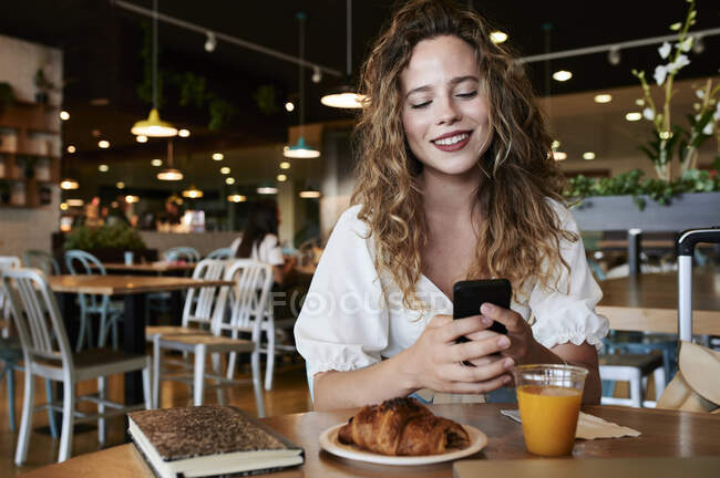 Smiling young woman using smartphone in a cafe while having breakfast — Stock Photo