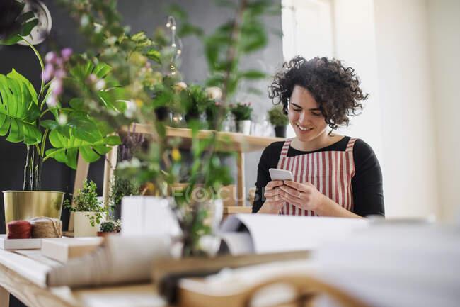 Посміхаючись, молода жінка користується мобільним телефоном у маленькому магазині з рослинами. — стокове фото