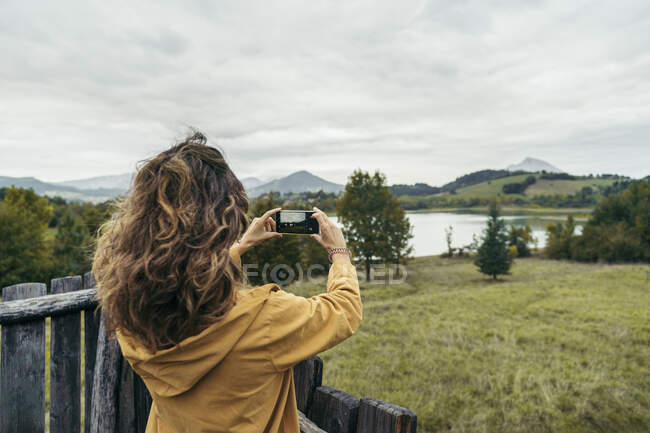 Young woman wearing yellow coat taking a photo with her smartphone — Stock Photo