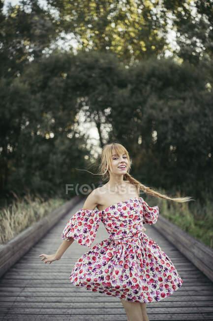 Retrato de jovem feliz usando vestido de verão com design floral dançando no calçadão — Fotografia de Stock