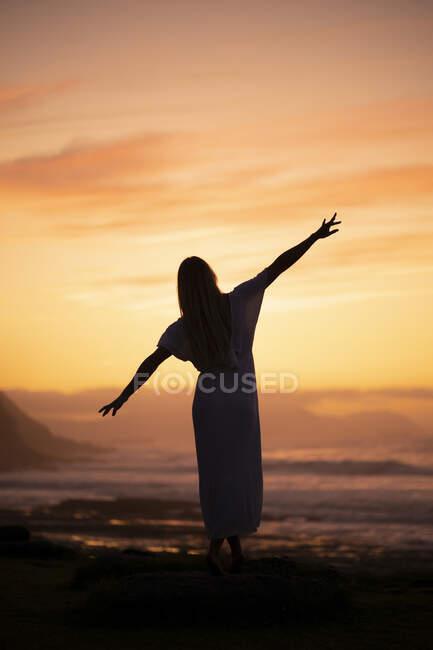 Silueta de mujer joven al amanecer en la playa - foto de stock