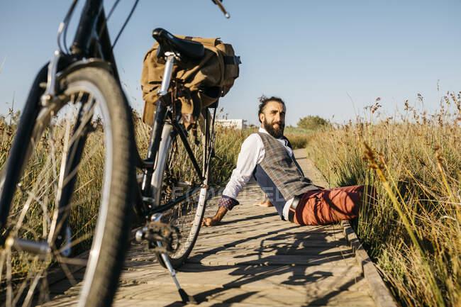 Хорошо одетый мужчина сидит на деревянной дорожке в сельской местности рядом с велосипедом — стоковое фото