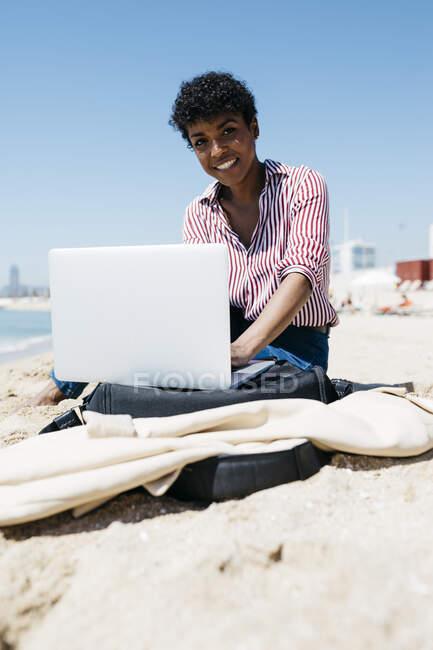 Жінка сидить на пляжі, працюючи з ноутбуком. — стокове фото