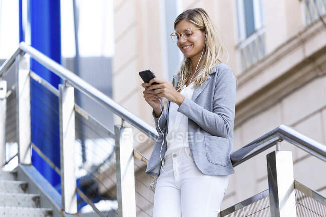 Young business woman texting with her mobile phone on stairs — Stock Photo