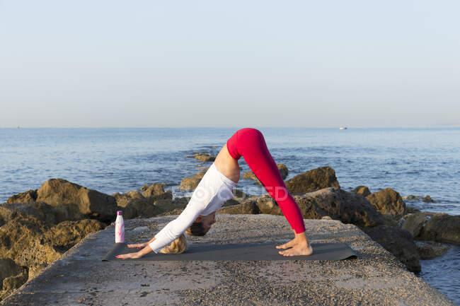 Молодая женщина практикует йогу на пляже, делает повернутую вниз собаку — стоковое фото