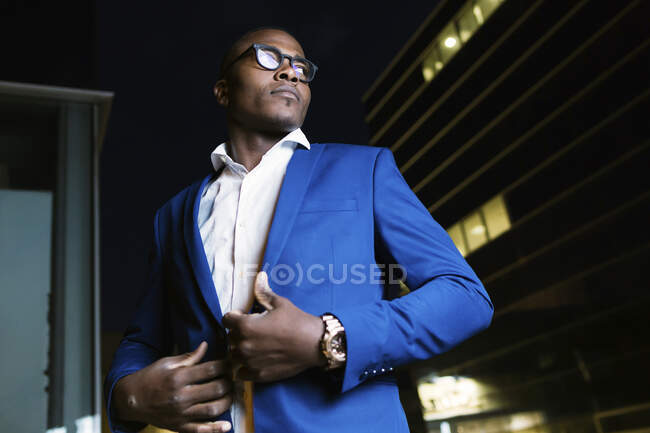 Young businessman wearing blue suit jacket, ooking sideways at night — Stock Photo