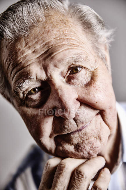 Portrait of senior man with hand on chin, close-up — Stock Photo