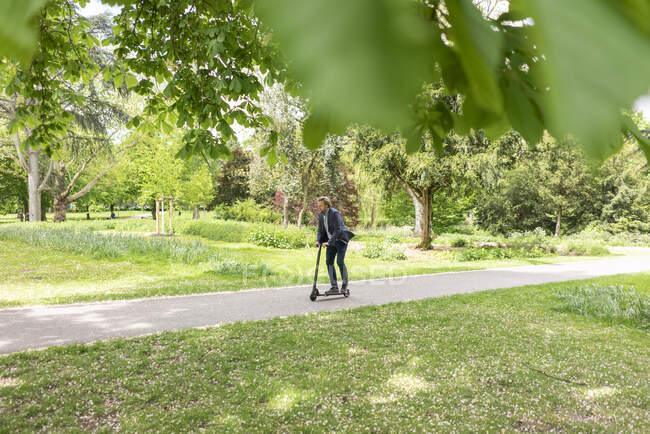 Empresário com E-Scooter no parque da cidade — Fotografia de Stock