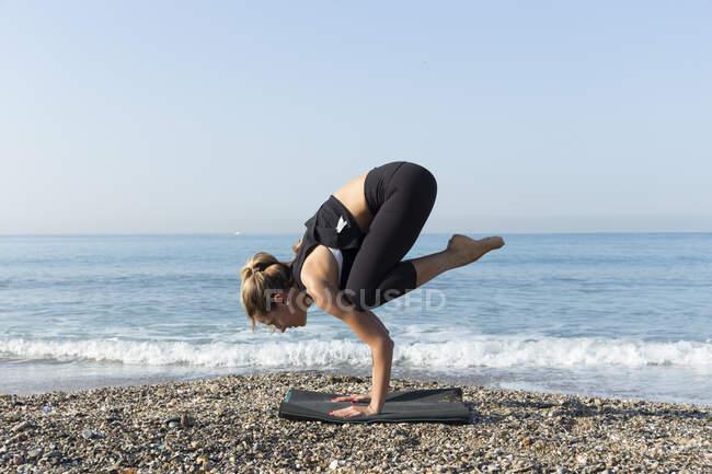 Молодая женщина практикует йогу на пляже, делает позу журавля, kakasana — стоковое фото