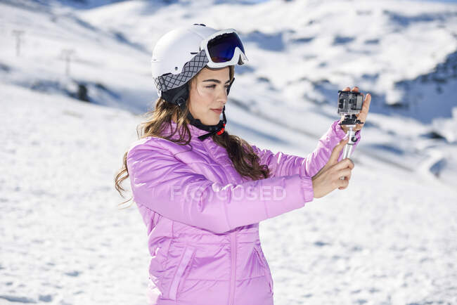 Woman in ski clothes filming with an action camera in snow covered-landscape — Stock Photo