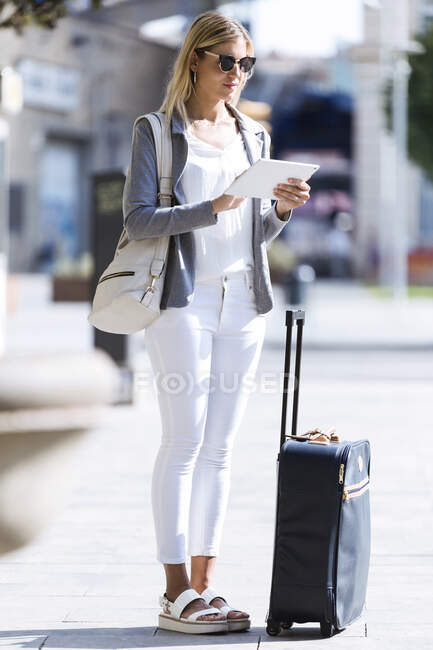 Young businesswoman working with digital tablet while standing with suitcase in the street — Stock Photo