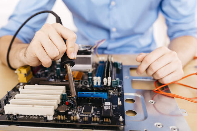 Close-up of technician repairing a desktop computer, soldering a component with tin — Stock Photo