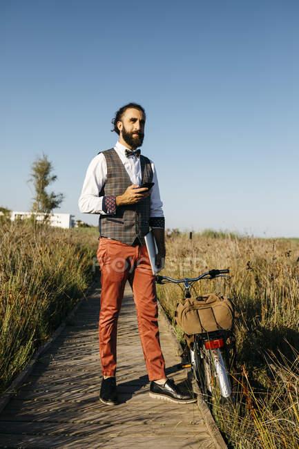 Хорошо одетый человек с велосипедом на деревянной дорожке в сельской местности отдыхает — стоковое фото