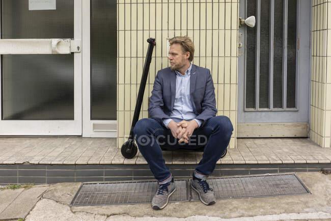 Бізнесмен з E-Scooter сидить на крок перед будинком — стокове фото