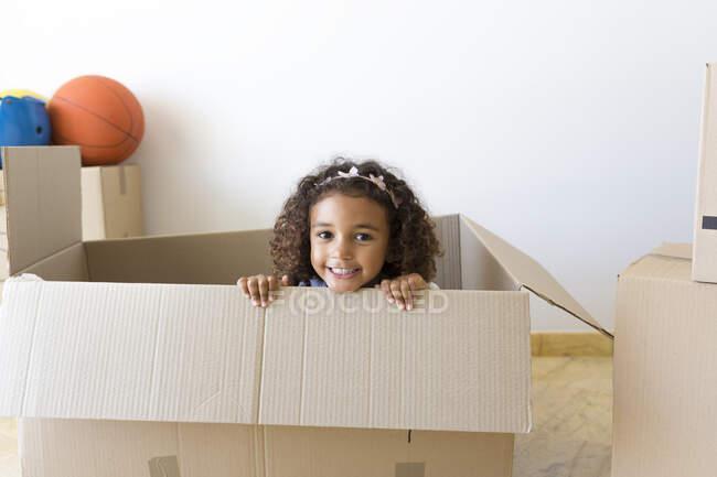 Retrato de menina feliz olhando para fora da caixa de papelão em nova casa — Fotografia de Stock