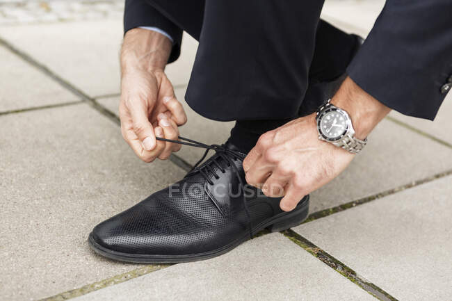 Businessman tying his shoe on pavement, close-up — Stock Photo