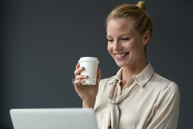 Giovane donna d'affari sorridente con laptop e caffè da asporto — Foto stock