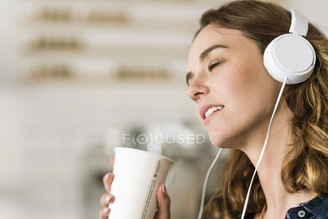 Mujer joven en la cafetería escuchando música con auriculares - foto de stock