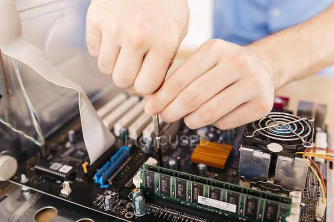Nahaufnahme eines Technikers, der einen Desktop-Computer mit einem Schraubenzieher repariert — Stockfoto