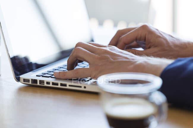 Mãos masculinas usando um laptop na mesa — Fotografia de Stock