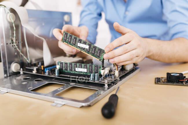 Nahaufnahme eines Technikers, der einen Desktop-Computer repariert und dabei den Arbeitsspeicher des Computers verändert — Stockfoto