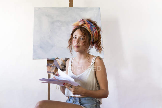Portrait of young female painter in art studio next to empty canvas — Stock Photo