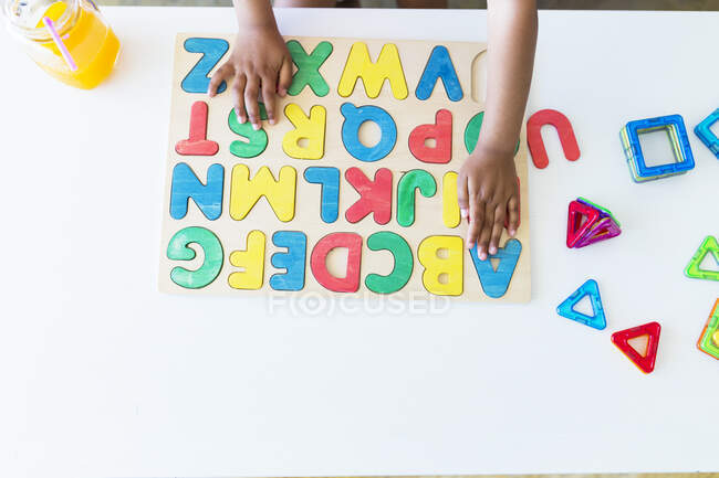 Primo piano di ragazza che gioca con alfabeto gioco di apprendimento sul tavolo — Foto stock