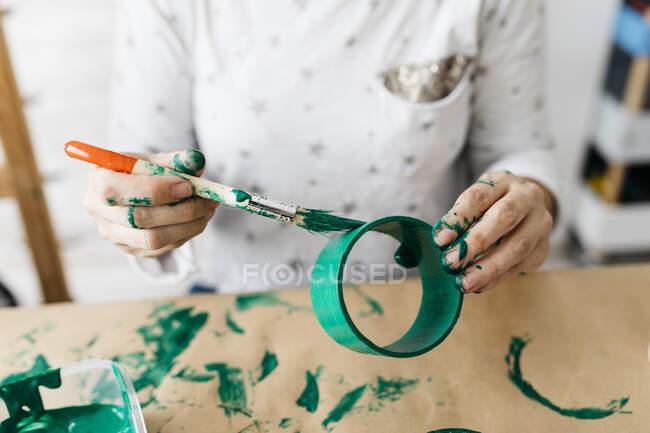 Frauenhände malen mit einem grünen Pinsel eine Rolle Pappe — Stockfoto
