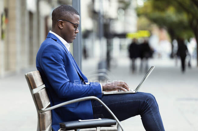 Young businessman wearing blue suit jacket sitting on bench and using laptop — Stock Photo