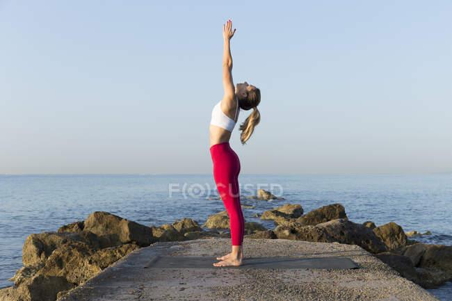 Молодая женщина практикует йогу на пляже, делает солнечные приветствия — стоковое фото