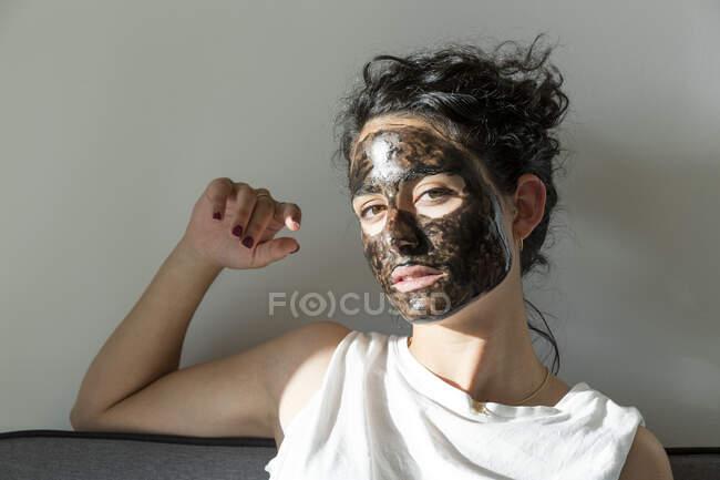 Retrato de jovem mulher usando máscara facial em casa — Fotografia de Stock