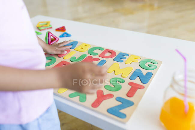 Зв'язок дівчини з іграми для навчання алфавіту на столі — стокове фото
