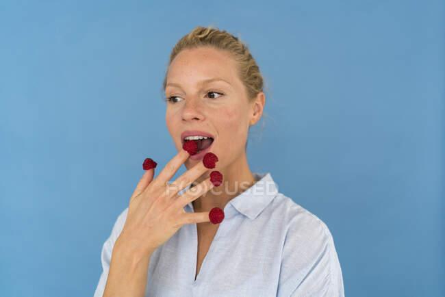 Portrait de femme blonde avec des framboises sur les doigts — Photo de stock
