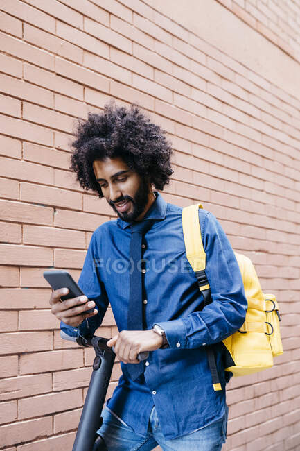 Portrait of smiling young man with backpack and E-Scooter looking at cell phone in front of brick wall — Stock Photo