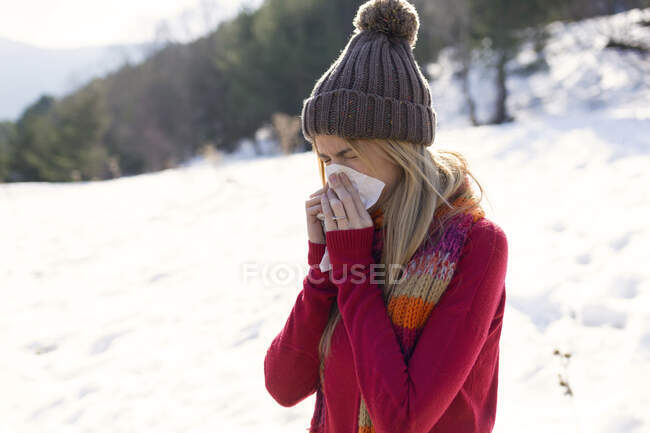 Young blond woman blowing nose in winter — Stock Photo
