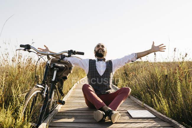 Feliz homem bem vestido sentado em uma passarela de madeira no campo ao lado de uma bicicleta — Fotografia de Stock