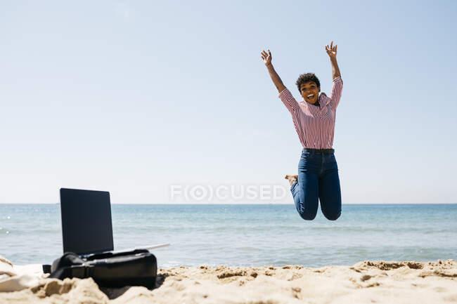 Жінка стрибає на пляж, лептоп на мішку. — стокове фото